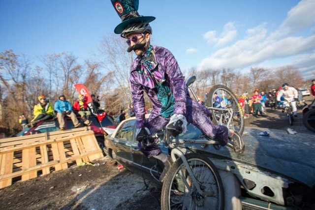 A costumed rider falls over a carhood at the Bilenky Junkyard Cross Race for the SSCXWC in Philadelphia, PA.