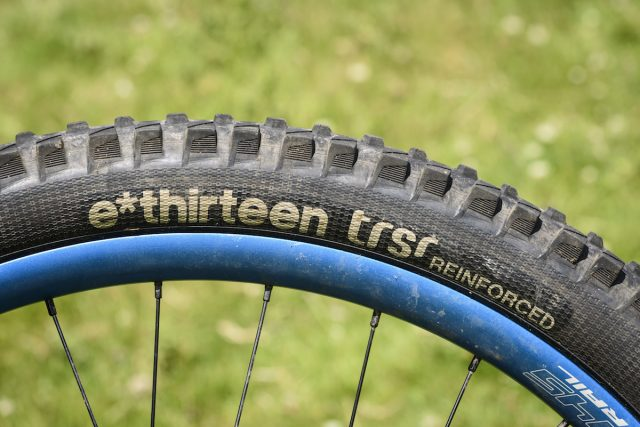 Joining e*thirteen's ever-expanding product line-up last year, the e*thirteen TRSr is intended to slot in between lightweight cross-country tyres and super-burly downhill tyres – in the words of Goldilocks, not too hot and not too cold, but juuuust right. Or to put it another way, a regular trail tyre for everyday use. That might be doing these tyres a slight disservice though, as they've performed brilliantly throughout the test and are more than 'just right'. Available in 27.5in and 29in options, with folding bead, reinforced sidewalls, reinforced pinch flat zones and enduro casing, they tip the scales at 918g (27.5in, 900g quoted) and are designed to pop up tubeless with just a track pump and a scoop of sealant. True to their word they went up without needing a compressor on every rim we tried, every time. Available in two compounds (Race or Plus), we've been riding the softer, grippier, Race compound which is made up of 70a rubber at the base, 42a in the centre, and a 40a for the side knobs. Given how soft the tyres feel under the thumbnail, they rolled along really well, and were only a bit draggy on long road sections. Once up to speed and onto the fun stuff though, that drag wasn't noticeable, and the payoff was that they provided ample grip for climbing, especially when faced with things like slanted wet rock or rooty madness sections. If outright climbing traction isn't required, you might want to consider either the harder compound TRS+, or a modern semi-slick such as the Maxxis Minion SS. The sidewalls felt really supportive and I often found myself running less pressure than I thought – sometimes as low as 22/24 psi front/rear, with very little tyre body roll, while on rockier Lakeland descents we upped the pressures slightly. Even if you go fast enough to drift, the traction is super-reliable except on very loose marbley surfaces, where we have yet to find a tyre that works perfectly. With a carefully shaped and siped tread pattern reminiscent of a Magic Mary, they offer great grip in mud and slop too, with lots of clearance, and the rubber was soft and edgy enough to keep things under control for braking when the going got loose. On the first off-road descent of the first ride on the tyre, we managed to put a hole in the rear that needed two tubeless plugs to seal. However, after that, it has been puncture and trouble free for over a year, even hitting long rocky Lakeland descents where we could feel the tyres bottoming out and carbon rims impacting on the ground below. As such, the pair of tyres on test has done a hard week of descending in the Pyrenees, many rides around Calderdale, trips to Peebles, and finally they've ended up here in the Lakes. They've not been ridden every day as they've been on a 'weekends and trips' bike, but we reckon they've done a good few hundred miles. While the rear is worn, they are looking surprisingly good for their age, and for the amount of riding time we've put into them in relation to the level of grip they return, the wear has been excellent and as they've worn the performance hasn't fallen away as dramatically as it has with other tyres on test. Overall There is no denying that at £59.95, they're at the upper-mid end of the price spectrum, but we've really got on well with these tyres, If you think of them as track day tyres for your sports car, it's well worth getting a pair for racing and Alps trips and maybe use something else for day-to-day riding.