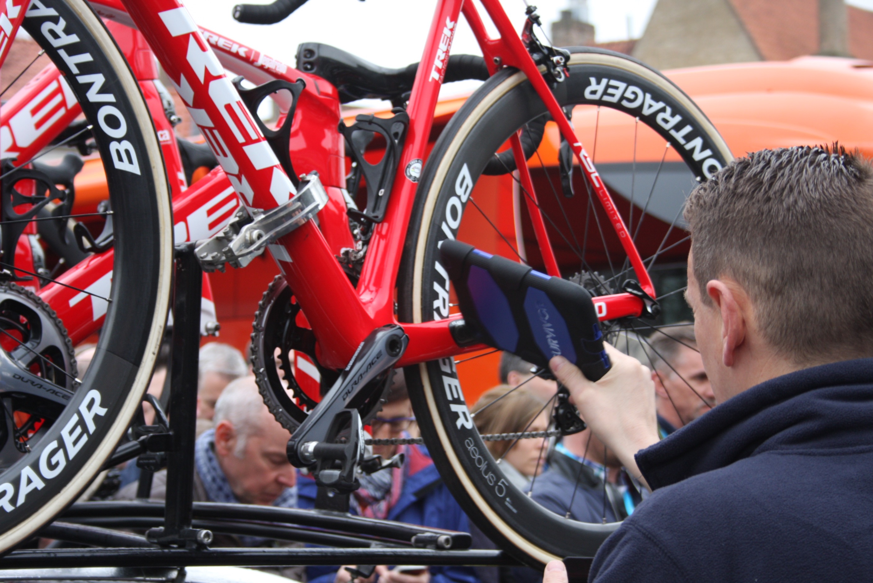 A UCI official waves the magic tablet around a bicycle frame before the start of the 2016 Tour of Flanders in an effort to stamp out technological fraud.